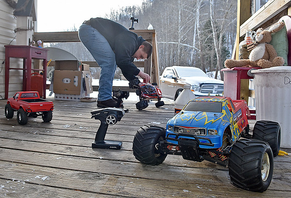 (Brad Davis/The Register-Herald) 14-year-old Joe Watson turns his front porch into a mini garage area as he tries to get a couple of his much more powerful and faster 1/8 scale R.C. cars (sitting at right and being worked on by Watson) to run in the bitter cold Sunday afternoon at his Wyco Hollow Road home.
