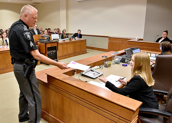(Brad Davis/The Register-Herald) The bailiff hands an item to the court clerk to be marked a mock trial with middle and high homeschoolers from the Appalachian Christian Academy in Raleigh County Ciruit Court Monday afternoon.