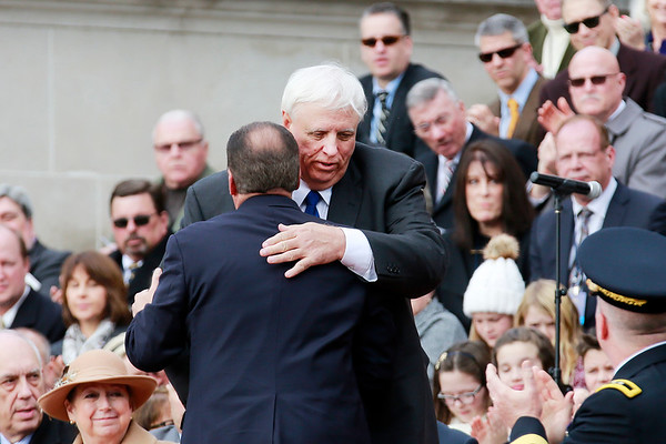 Governor Earl Ray Tomblin hugs Governor-elect Jim Justice prior to his oath of office as the 36th Governor of the State of West Virginia at the Capitol in Charleston on Monday. (Chris Jackson/The Register-Herald)