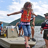 (Brad Davis/The Register-Herald) Facepainted 8-year-old Talcott resident Abigail Reed leaps from the boat after speedy ride on the water during the Safety on The Blue event Sunday afternoon at Bluestone Lake.