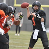 (Brad Davis/The Register-Herald) West (black jerseys) quarterback McLeod Bethel-Thompson is flushed from the pocket by East (orange jerseys) pass rushers Ollie Ogbu, far left, and Patrick McNeil during the opening game of The Spring League Saturday afternoon in White Sulphur Springs.