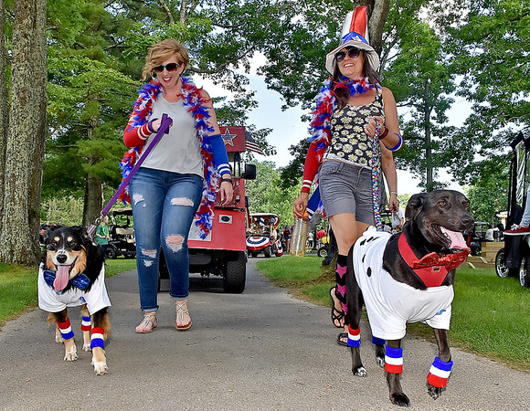 (Brad Davis/The Register-Herald) Adrienne Wilson, left, walks Mugsy and Zennia Jennie walks Maya during a special 4th of July Golf Cart Parade Saturday evening at Glade Springs as part of their 4th of July Celebration weekend.