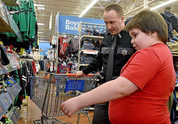(Brad Davis/The Register-Herald) Nine-year-old Kyle Farris checks out t-shirts and other clothes with Raleigh County Sheriff's Deputy H.W. Long, II during a special Shop With a Deputy event Sunday afternoon at the MacArthur Walmart. Several Raleigh County Sheriff's Deputies and West Virginia State Troopers spent the day taking kids around the store with $100 budgets to spend on whatever they chose.
