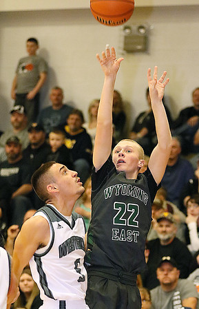 (Brad Davis/The Register-Herald) Wyoming East's McQuade Cannada gets away a three-point shot before Westside defender Shawn Jenkins can get there during the Warriors' win over the county rival Renegades Friday night in Clear Fork.