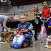 (Brad Davis/The Register-Herald) Two-year-old Dailon House motors around the floor as activity buzzes during the annual Mac's Toy Fund event Saturday morning at the Beckley-Raleigh County Convention Center.