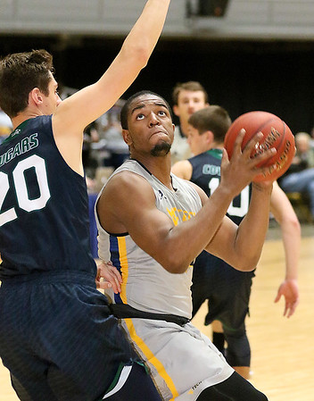 (Brad Davis/The Register-Herald) WVU Tech's Nequan Carrington drives and scores as Mount Vernon Nazarene's Brett Vipperman defends Tuesday night at the Beckley-Raleigh County Convention Center.
