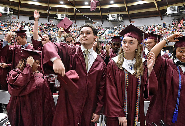 (Brad Davis/The Register-Herald) Woodrow Wilson seniors reach for their caps to toss them into the air at the conclusion of the school's 91st Commencement Saturday evening at the Beckley-Raleigh County Convention Center.