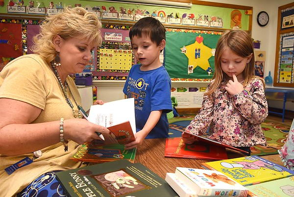 Andrea Martin, pre-k teacher, writes her students names in books theyt picked out during the Snuggle & Read program held at Mount Hope Elementary School Wednesday morning morning.<br /> (Rick Barbero/The Register-Herald)