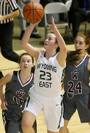 (Brad Davis/The Register-Herald) Wyoming East's Katie Daniels drives to the basket as George Washington's Dee McMillan, left, and Morgan Hotsclaw defend during Big Atlantic Classic action Wednesday night at the Beckley-Raleigh County Convention Center.