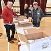 (Brad Davis/The Register-Herald) Volunteers wait for more to-go meals before setting out to make deliveries around the area during Lewis Christian Community Center's Thanksgiving dinner Thursday afternoon in Oak Hill.