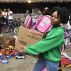 (Brad Davis/The Register-Herald) Volunteer Lauren Washington helps customers gather items during the annual Mac's Toy Fund event Saturday morning at the Beckley-Raleigh County Convention Center.