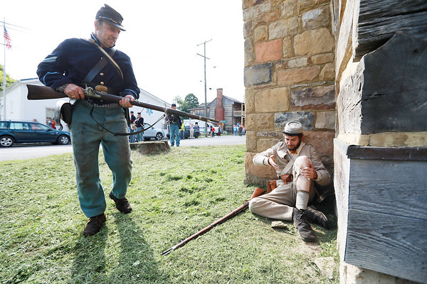 Civil War re-enactor Joseph Rose, from Pocahontas County, is taken prisoner by a Federal Army infantry member during a  battle between the local Home Guard and the Federal Army as part of Monroe County Heritage Day in Union on Saturday.  (Chris Jackson/The Register-Herald)