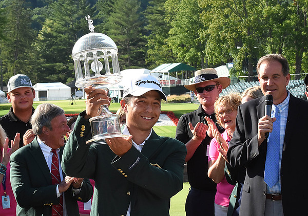 Jim Nanyz, CBS sportscaster, right, watches Xander Schauffele, lift up the winning trophy after winning The Greenbrier Classic.<br /> (Rick Barbero/The Register-Herald)