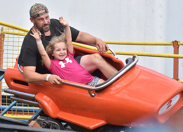 (Brad Davis/The Register-Herald) Seven-year-old White Sulphur Springs resident Kalianna Withrow throws her arms in the air as she and dad Jason Fury speed around a race car-themed rollercoaster during the State Fair Friday afternoon in Fairlea.