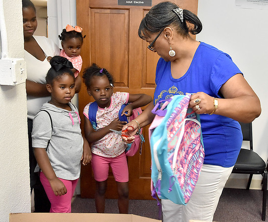 (Brad Davis/The Register-Herald) Young students Dejanae Mayo, right, and Naveah Powell get new backpacks from volunteer Vickie Hancock during the backpack distribution portion of Heart of God Ministries' Back to School Picnic Saturday afternoon.