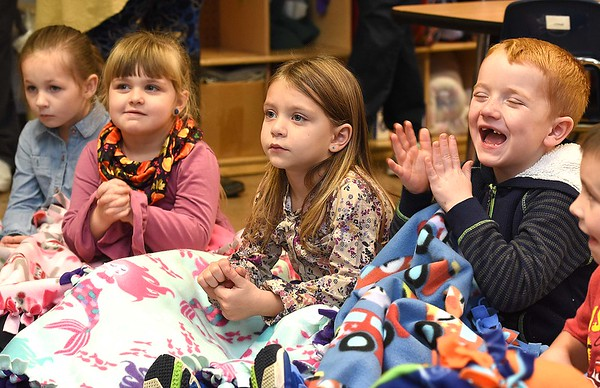 """Linda Cole, co-president Fayette Co. chapter Read Aloud West Virginia, reads Giraffes Can't Eden Biere, left, Kelly Brandstetter, Adalee Crawford T.J. Parson and Andrew Canady, are wrapped up in their blankets litening to, Linda Cole, co-president Fayette Co. chapter Read Aloud West Virginia, read """"Giraffes Can't Dance"""" book to pre-k students during the Snuggle & Read program held at Mount Hope Elementary School Tuesday morning.<br /> (Rick Barbero/The Register-Herald)"""