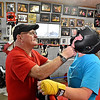 (Brad Davis/The Register-Herald) Long time boxing trainer Carl Murdock, left, helps Lewisburg resident and one of his former Toughman Contest fighters Candie Benedict with her headgear prior to a sparring session with one his current fighters, Amber Sweeney, inside his garage gym at his Mount Hope home Monday evening. The 70-year-old Murdock is widely considered to be one of the most effective at grooming local scrappers into polished boxers that win matches, with his Mount Hope Boxing Club producing some 40 champions male and female over a 30 plus year period. The walls of his garage gym are parts local boxing museum, hall of fame and champions' club. Each fighter who trains with him aspires to be on his wall one day. Benedict herself won a pair of middleweight championships training with Murdock, one in Lewisburg and another in Beckley.