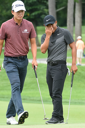 C.T. Pan, right, reacts after just missing his birdie putt on the 17th hole during the first round of The Greenbrier Classic. Watching to the left is Michael Kim.<br /> (Rick Barbero/The Register-Herald.com