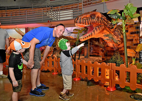 (Brad Davis/The Register-Herald) Fayetteville residents Ben Elmore and sons Oliver (left), 3, and Bishop, 4, explore a prehistoric world during a two-day weekend event called T-Rex Planet at the Beckley-Raleigh County Convention Center.