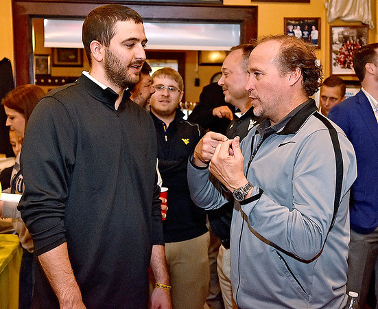 (Brad Davis/The Register-Herald) Beckley resident Kyle Muscari has a candid conversation with West Virginia football coach Dana Holgorsen during the opening moments of the WVU Coaches' Caravan stop at Calacino's Thursday evening.