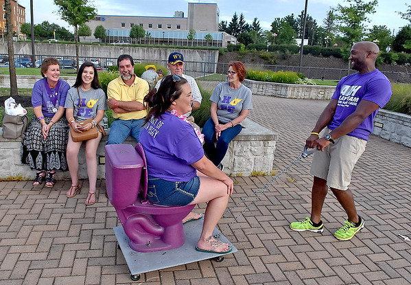 """(Brad Davis/The Register-Herald) Team ARH's Amanda Jones is bestowed the honor of riding the """"Purple Princess"""" as she's pulled by Micah Harris during the American Cancer Society's Relay for Life atop Beckley's Intermodal Gateway Friday night. Anyone chosen to ride the ceremonial toilet was tasked with raising a certain amount of money in donations before they could get off the pot."""