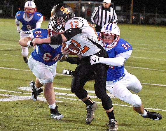 (Brad Davis/The Register-Herald) Summers County's Jacob McBride fights for yardage as he's dragged down Midland Trail's Adam Gill, right, and Hunter Jones after a big gain Friday night at Nicholas County High School.