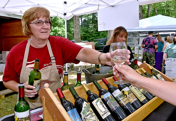 (Brad Davis/The Register-Herald) Lynne Stone, co-owner of Stone Road Vineyard in Elizabeth, hands out samples of their fine wine during Daniel Vineyards' 19th Annual Spring Wine Festival Saturday afternoon in Crab Orchard.
