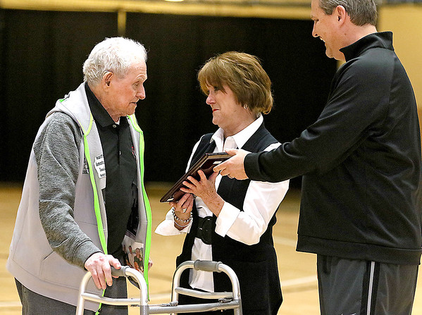 (Brad Davis/The Register-Herald) Longtime area basketball fixture Lewis D'Antoni, left, receives a special plaque for his years of service from Scott Brown's mother Beverly during a break in the Scott Brown memorial game Saturday evening at the Beckley-Raleigh County Convention Center.