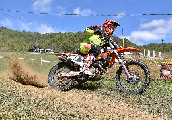 (Brad Davis/The Register-Herald) A competitor kicks up dirt as he whips around a turn during Sprint Enduro Series dirt bike racing Saturday afternoon at Hidden Valley Golf in Glen Daniel.