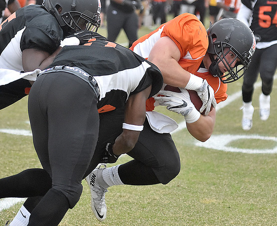 (Brad Davis/The Register-Herald) North (orange) fullback Adam Cox drags a pair of South (black) defenders as he rumbles ahead after making a catch during Spring League action Sunday afternoon in White Sulphur Springs.