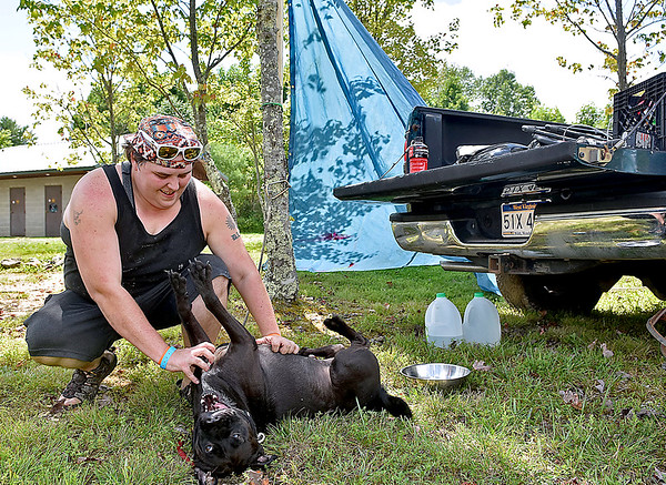 (Brad Davis/The Register-Herald) Charleston resident Kim Shrader takes a break from setting up camp to play with Gonzo, her 3-year-old pitt bull/lab mix companion, during the opening hours of the Cluster Music & Arts Festival going on this weekend at Ace Adventure Resort Thursday afternoon in Minden. Shrader, a co-owner of Hole in the Wall Studios which specializes in blacklight art, came with a large group of fellow Charlestonians to the 2nd annual event, which was held in Flatwoods last year. Running through Sunday afternoon, it's a smaller event than the annual Mountain Music Festival but comes with a similar crowd and vibe.