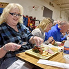 (Brad Davis/The Register-Herald) Charleston resident Dee Dizmang, left, sits down to start digging into a plate of ramps and other hot food during Richwood's Feast of the Ramson Saturday afternoon at Cherry River Elementary School.
