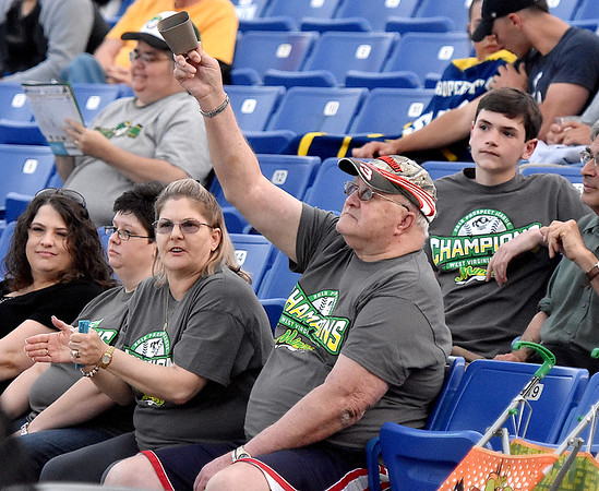 (Brad Davis/The Register-Herald) West Virginia Miners fan Ken Scarbro lets his cowbell ring out as he and wife Michelle (clapping at left) take in the action during the team's home opener against the Butler Blue Sox Thursday night at Linda K. Epling Stadium.