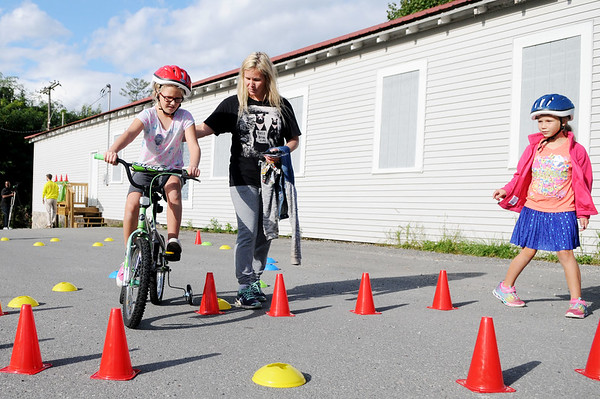 "Nikki Glende, from Hico, helps her daughter Charlotte, 9, navigate a course as her other daughter, Victoria, 7, watches during ""bike rodeo"" as part of the Kids Classic McManus Trail Event in Beckley on Thursday. (Chris Jackson/The Register-Herald)"