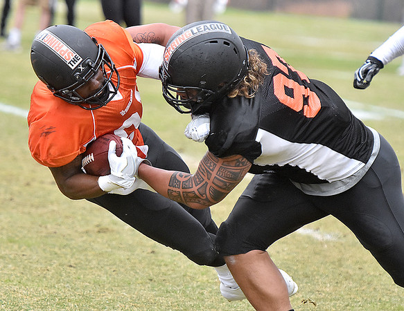 (Brad Davis/The Register-Herald) North (orange) running back Zachary Bauman is driven down by South (black) defensive lineman Tani Toupou during Spring League action Sunday afternoon in White Sulphur Springs.