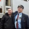 (Brad Davis/The Register-Herald) Retiring Amtrak Engineer Dennis Gleason, right, is congratulated by colleague and New River Train Excursion narrator Davy Neal during Hinton Railroad Days Sunday afternoon. Gleason retires with 40 years of service for Amtrak.