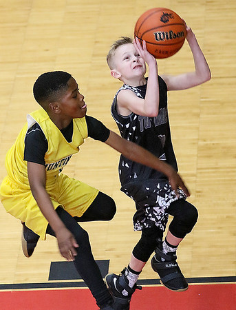 (Brad Davis/The Register-Herald) Tug Valley's Ethan Ferral (right) drives to the basket as Huntington Gold's Zah Jackson during a 4th grade Biddy Buddy game Saturday at the YMCA.