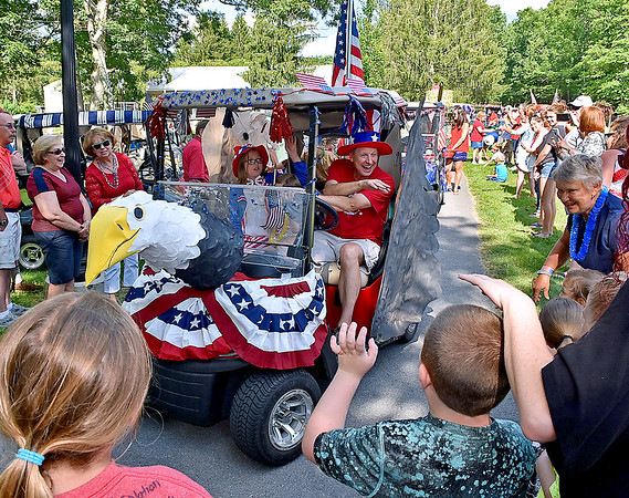 (Brad Davis/The Register-Herald) A bald eagle-themed cart piloted by Rennie Hill and Uncle Sam, a.k.a. his granddaughter Hailey Frame, 8, wave at spectators as they make their way through Town Square during a special 4th of July Golf Cart Parade Saturday evening at Glade Springs as part of their 4th of July Celebration weekend. Not photographed on the back of their cart, which even had wings, are Hill's granddaughter Ellie, dressed as the Statue of Liberty and Addisyn Harris, dressed as Pocahontas.