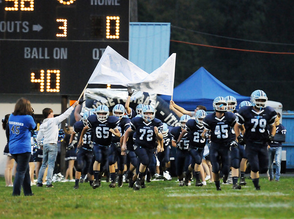 Members of the Meadow Bridge football team run onto the field prior to kickoff of their game against Fayetteville Friday in Meadow Bridge. (Chris Jackson/The Register-Herald)