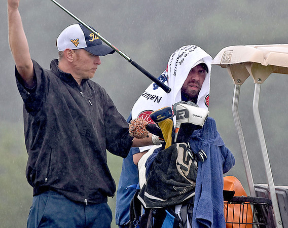 (Brad Davis/The Register-Herald) Tony Giles, left, and Jeff Miller try to deal with the elements as they get ready for their next shots during BNI action Saturday afternoon at Grandview Country Club.