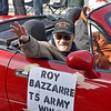 (Brad Davis/The Register-Herald) World War II veteran Roy Bazzarre tosses candy to youngsters in the crowd as he rides along during the annual Veterans Day Parade Saturday morning.