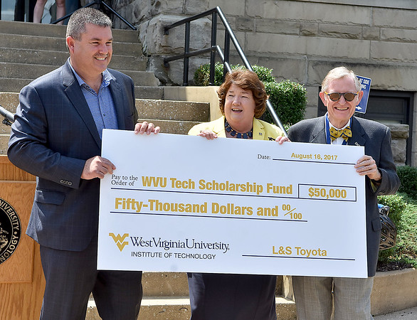 (Brad Davis/The Register-Herald) WVU Tech President Carolyn Long and WVU President E. Gordon Gee accept a $50,000 donation from L&S Toyota owner Shawn Ball following a brief ceremony marking the first day of classes for Tech on the Beckley campus Wednesday afternoon.