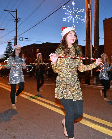 (Brad Davis/The Register-Herald) Participants from the Fayetteville High School marching band twirl candycanes as they take part in the town's annual Christmas Parade Friday night.