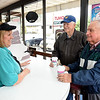 Lynn Plumley, left, talks with two of her cusrtomers, Ernest Nichols and Andy Moscarito at the Donut Connection.<br /> (Rick Barbero/The Register-Herald