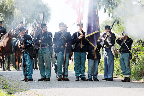 Civil War re-enactor Federal Army infantry fire at the local Home Guard on Pump St. during a battle between the local Home Guard and the Federal Army as part of Monroe County Heritage Day in Union on Saturday.  (Chris Jackson/The Register-Herald)