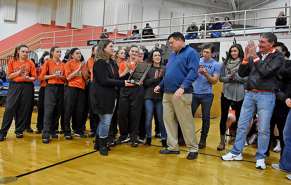 "(Brad Davis/The Register-Herald) Former Summers County Lady Bobcats basketball coach Wayne Ryan, middle in blue, receives a special plaque from principal Kari Vicars surrounded by his family, friends, current and former players during a court dedication ceremony in his name Friday night in Hinton. It will now be known as the ""Coach Wayne Ryan Court."""