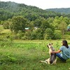 Pamela Bailey looks over the Five Springs Farm with her dog Hazel she owns on Shelter Road in Fayetteville.<br /> (Rick Barbero/The Register-Herald)