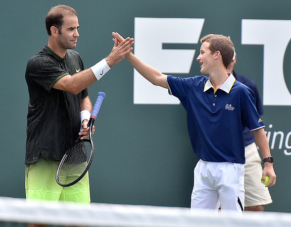(Brad Davis/The Register-Herald) Ballboy Jaxen Ransom gets a high-five from tennis legend Pete Sampras after getting to plays against James Blake during the Greenbrier Champions Tennis Classic Saturday afternoon in White Sulphur Springs.