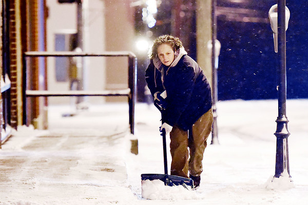 """Beckley resident Kim Ledford works to clear a downtown building's sidewalk from snow on Prince St. as temperatures dip into the 20s on Tuesday evening in Beckley. """"This is typical Beckley weather,"""" said Ledford. """"There's something kind of refreshing about the first snow. It clears out all the old gunk - it clears your mind."""" (Chris Jackson)"""