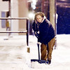 "Beckley resident Kim Ledford works to clear a downtown building's sidewalk from snow on Prince St. as temperatures dip into the 20s on Tuesday evening in Beckley. ""This is typical Beckley weather,"" said Ledford. ""There's something kind of refreshing about the first snow. It clears out all the old gunk - it clears your mind."" (Chris Jackson)"